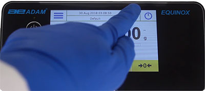 Gloved hands can use the Adam Equinox touchscreen analytical balance